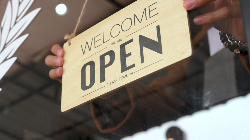 Business owner hanging we're open sign on front door. Reopening activity after lockdown, ended the lockdown and quarantine. | Shutterstock HD Video #1058074276