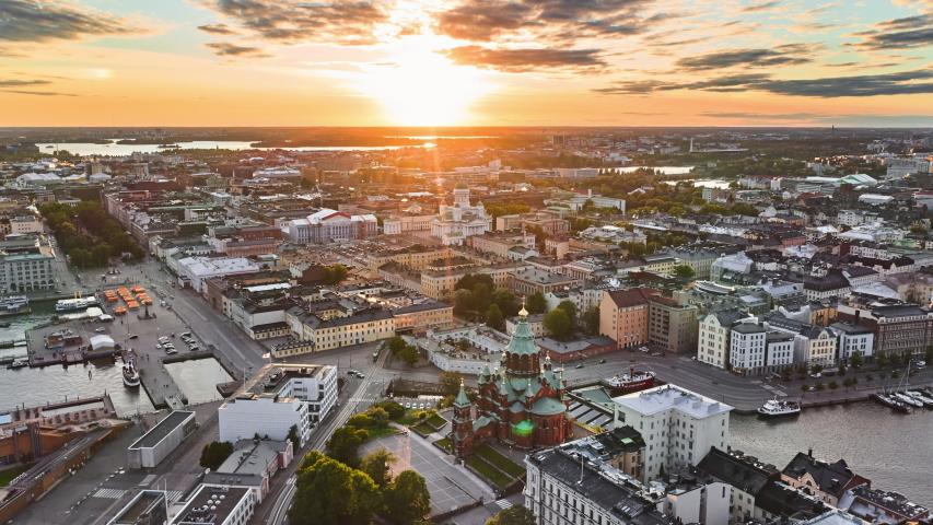 Helsinki, Finland - August 11, 2020: Aerial view of Uspenski Cathedral, St Nicholas' Church, beautiful sunset on the background, Helsinki, Finland. Aerial hyperlapse / timelapse.