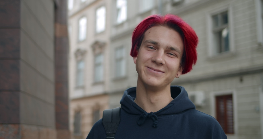 Portrait of young hipster man with red dyed hair looking to camera. Close up view of millennial guy in dark hoodie smiling while standing at street. Concept of people emotions | Shutterstock HD Video #1058075713