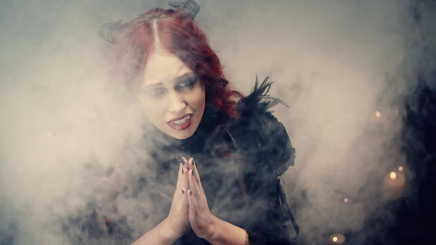 Red-haired girl witch with black horns sitting on floor in candlelight and praying with folded hands. Scary demon doing witchcraft. Halloween mystery rite. Ritual of Occultism or esoterics concept. | Shutterstock HD Video #1058082220