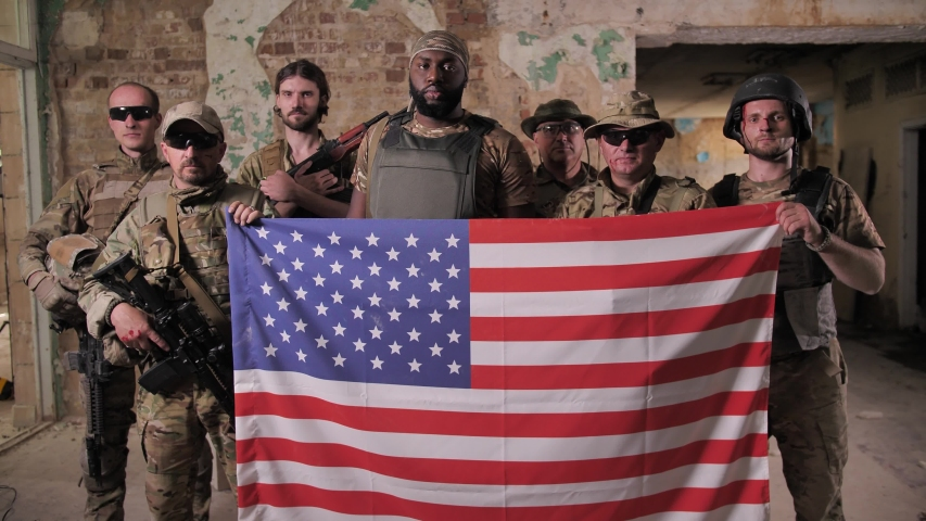 Serious multinational males soldiers in camouflage, bulletproof vests posing with US flag. Brave patriots of USA armed forces standing with weapons and holding symbol of United States of America