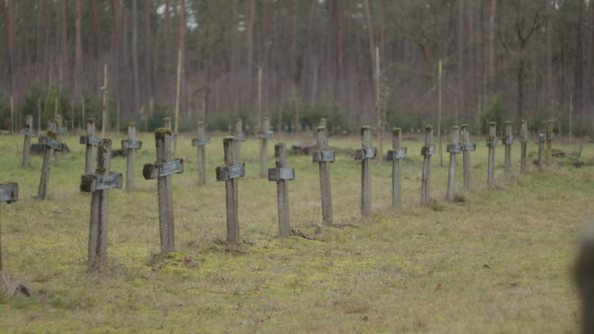 Panning over rows of old gravestones at abandoned graveyard