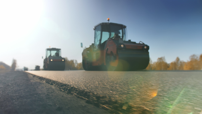 A layer of freshly laid asphalt in the rays of the setting sun. Road surface repair. Construction of a new road. The rollers level and compact the asphalt. Road rollers. Sun glare.   Shutterstock HD Video #1058087866
