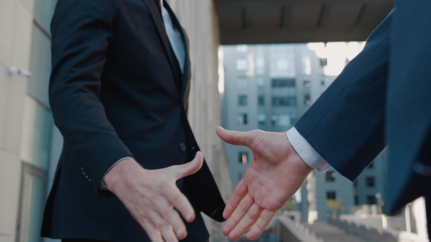 Close-up of two businessmen shake hands when meeting, agree to a deal or say hello. Handshake of two successful businessmen making a deal. Office building on background. Business district.