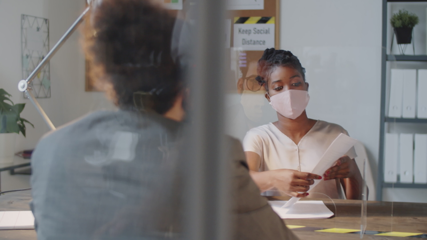 Afro-American businesswoman in face mask explaining and giving contract to Arab male partner for signing while working at office table with glass spit protection wall during covid-19 pandemic Royalty-Free Stock Footage #1058096563