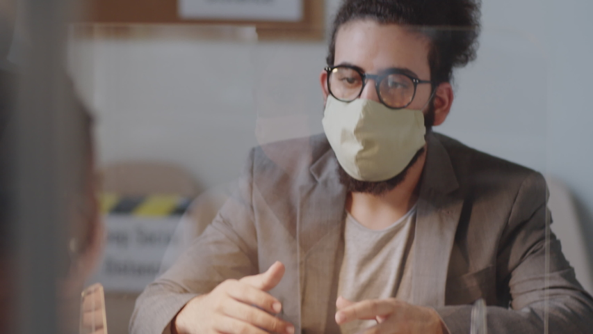 Young Arab man in face mask explaining something to afro-american female colleague through glass spit protection wall while working together in office during coronavirus pandemic Royalty-Free Stock Footage #1058096755