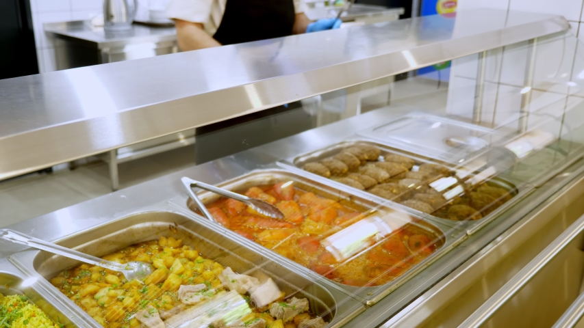 cooking. close-up. the waiter, in protective gloves , opens containers with meals, behind glass showcase, in self-service cafeteria or buffet restaurant. health food. volunteering and charity Royalty-Free Stock Footage #1058097472