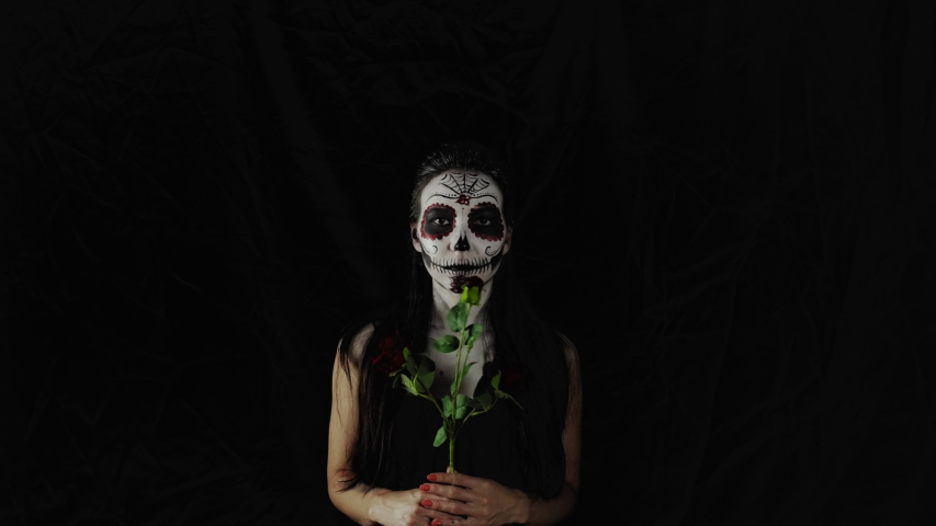 Halloween makeup. feamle with a rose in her hands. Portrait of a young woman with horrible colorful Halloween makeup on a dark background.  Royalty-Free Stock Footage #1058097583