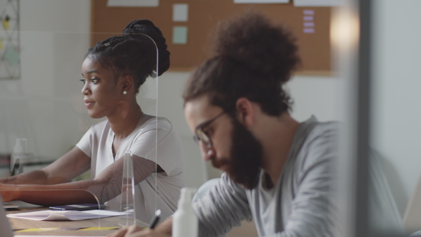 Afro-American woman and Arab businessman working on laptops and taking notes at office desk with glass spit protection wall during coronavirus outbreak Royalty-Free Stock Footage #1058098549
