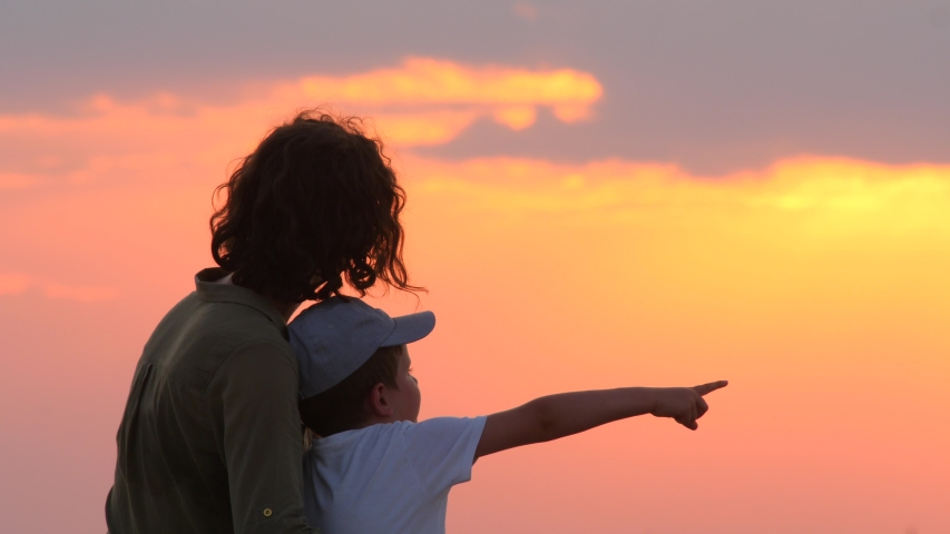 Mother with son watching sunset. One parent family. Loving mother spends time with child. Kid pointing to color of the dramatic sky while talking to mother. Positive emotions. Happiness concept