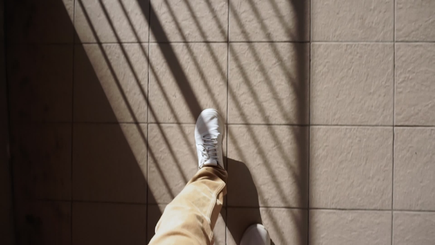 Man in white sneakers walks down the street on a bright Sunny day. pov video, first person | Shutterstock HD Video #1058099992