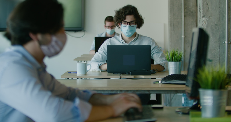 Office work during coronavirus. Employees maintain social distance. Masked managers typing on laptops. A modern company that cares about working conditions Royalty-Free Stock Footage #1058100160