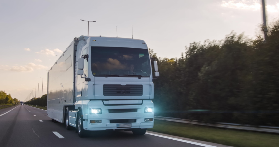 Cargo truck with cargo trailer driving on a highway. White Truck delivers goods in early hours of the Morning - very low angle drive thru close up shot. Royalty-Free Stock Footage #1058100298