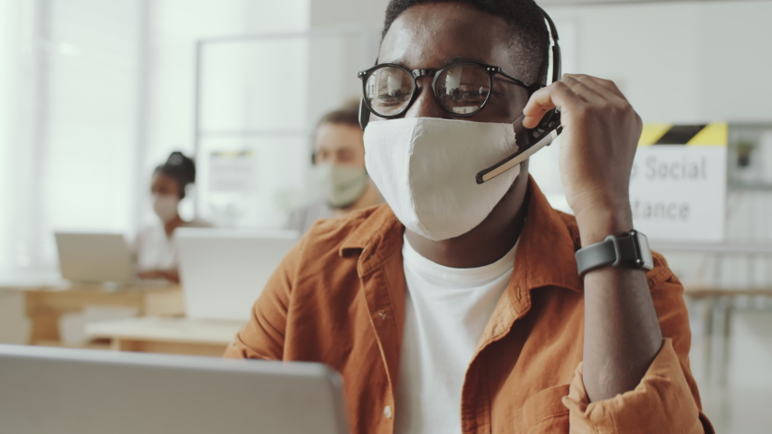 Young Afro-American man in protective face mask and headset talking on video call on laptop while working in office during coronavirus pandemic