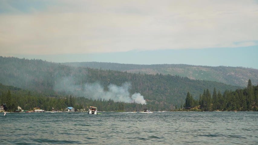 California Wildfire, mountain burns on edge of lake, helicopter drops water on smoke plume.
