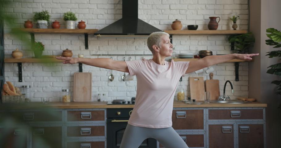 Healthy elderly senior woman doing yoga exercise at home