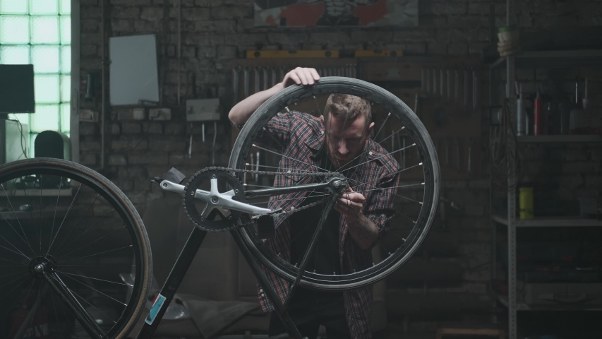 Atmospheric workshop, repair garage: a hipster man with a beard repairs a bicycle upside down. He pedals and looks at the spinning wheel. Bicycle repair, small business.