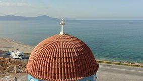Flies around the dome of a Christian temple and a cross against the background of the Mediterranean sea in Greece, aerial video