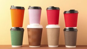 A lot of disposable cups for coffee and tea change places. Nice catering for a coffee shop. Video footage stop motion. Beige background.