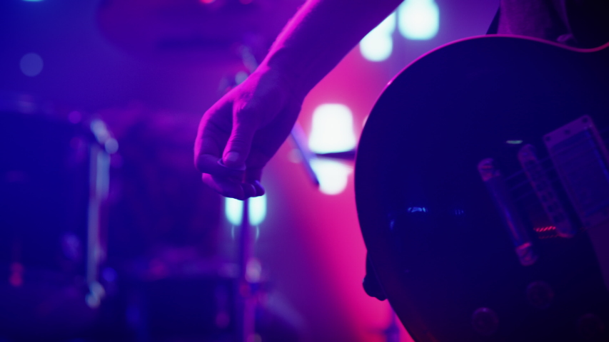 Rock Band Performing at a Concert in a Night Club. Close Up Shot of a Musician Holding and Dropping a Guitar Pick. Live Music Party in Front of Bright Colorful Strobing Lights on Stage.