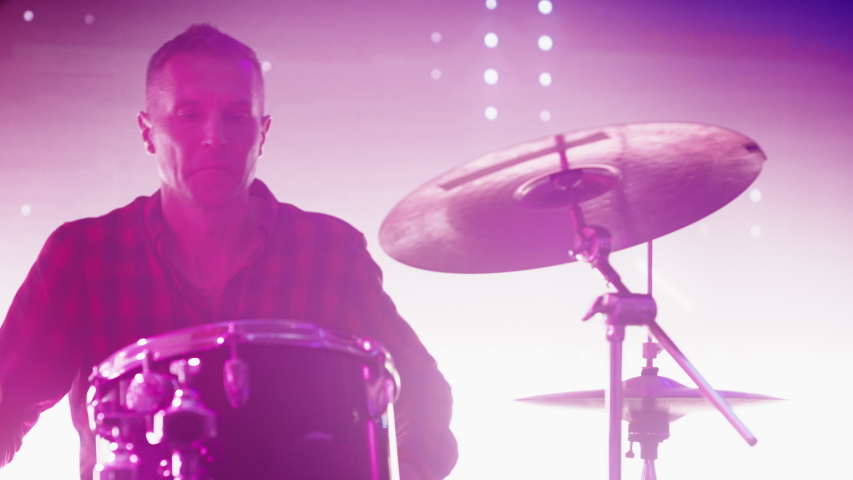 Rock Band Performing at a Concert in a Night Club. Close Up Portrait of a Drummer Playing the Drums. Live Music Party in Front of Bright Colorful Strobing Lights on Stage.