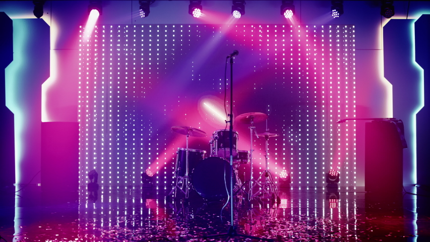 Empty Concert Stage in a Night Club. Professional Drum Kit and Other Music Equipment for Live Gig with Rock Band. Confetti on the Dance Floor. Bright Colorful Strobing Lights on Stage.