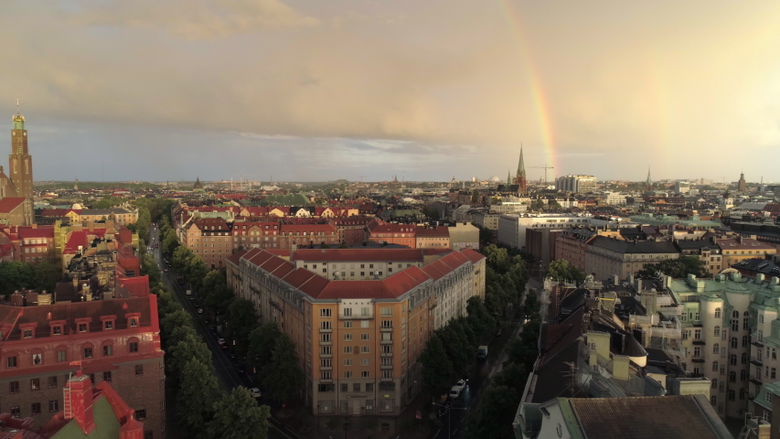 Rainbow over Stockholm city aerial view. Drone shot flying over buildings in central Stockholm, cityscape skyline at sunset, rainy sky Royalty-Free Stock Footage #1058127838