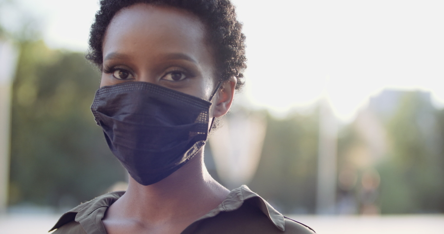Portrait of isolated ethnic girl standing in street putting on black medical mask on female African face, protecting herself from covid virus, pandemic time, pollen allergy seasonal disease, close up Royalty-Free Stock Footage #1058134342