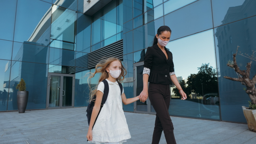 Adult woman in classic clothes holds little girl in dress by hand, talking together, walking down street. Family wears protective medical masks from virus, allergy. Mom picks up daughter from school Royalty-Free Stock Footage #1058137120