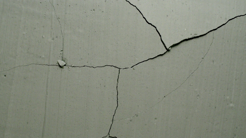 Effect of a grey concrete wall cracking from center from the Impact collection - Debris VFX Video Element.