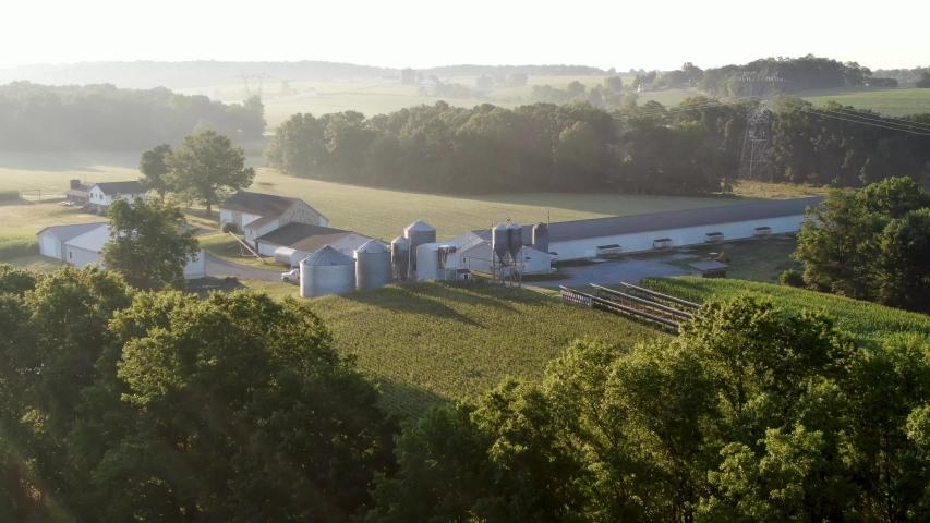 Establishing shot, aerial of family farm in United States, grain bins, chicken house, barn and fields in summer hazy foggy morning light