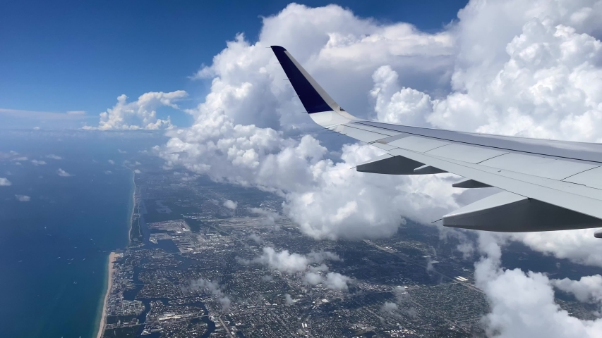 Flying over Miami. View of east coast from plane's window. Beautiful white clouds against blue sky. The turquoise waters of Atlantic coast | Shutterstock HD Video #1058147254