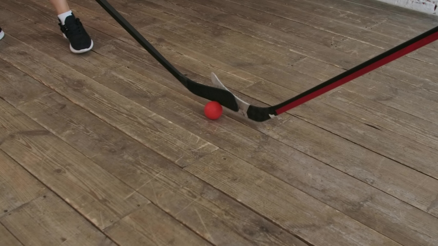 Hockey sticks hitting hockey red ball. Home practice floor hockey. A team game of two players. Slow motion. Close up. | Shutterstock HD Video #1058156986