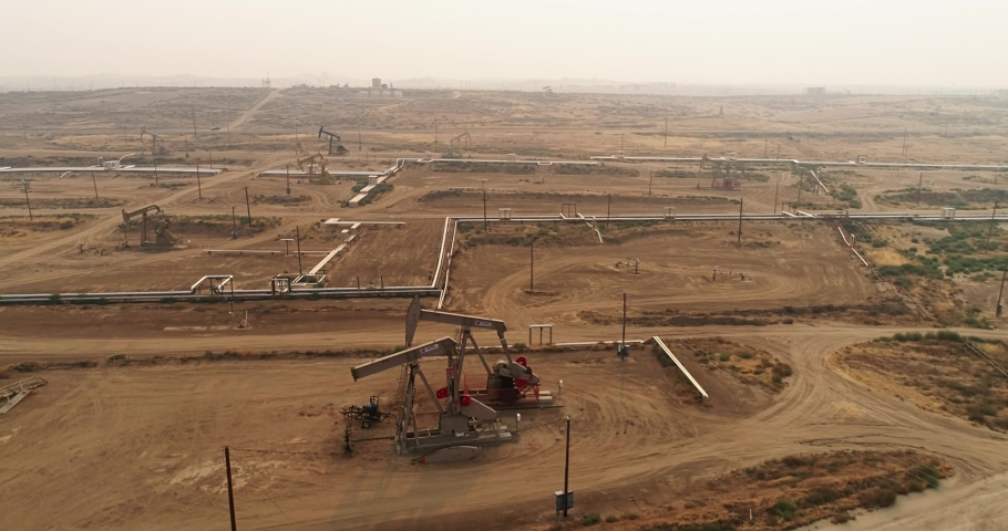 Pump jack in vast oil fields in California. Pipelines transporting oil from oil pumps, aerial drone shot Royalty-Free Stock Footage #1058157046