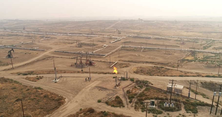 Gas flare coming out of a flare stack in California, vast oil fields with pipelines transporting oil from oil pumps, aerial drone shot Royalty-Free Stock Footage #1058157049