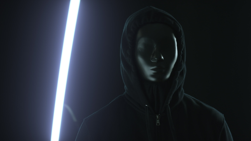 Anonymous rioter wearing black mask and hood in front of glowing lights. Protest or secrecy concepts | Shutterstock HD Video #1058162812