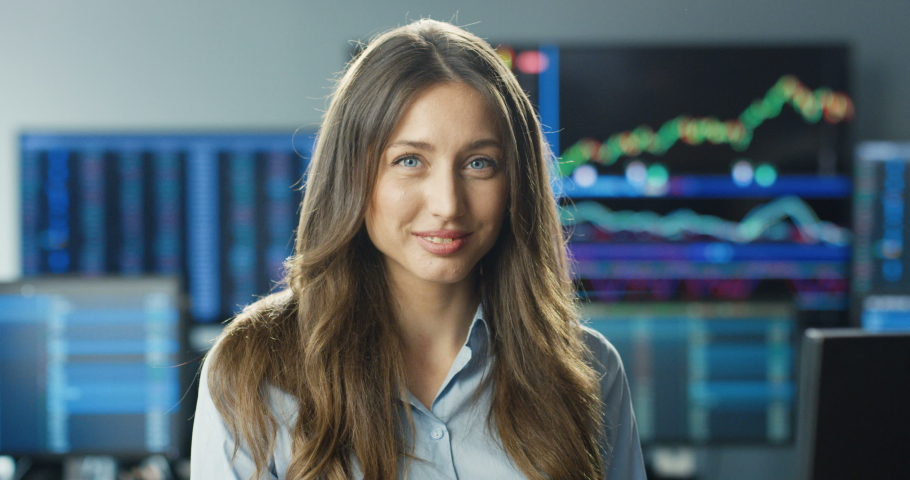 Portrait of young Caucasian beautiful woman trader with long hair looking at camera and smiling in trading office of exchange stock market. Monitors with charts, graphics and numbers on background. Royalty-Free Stock Footage #1058170243