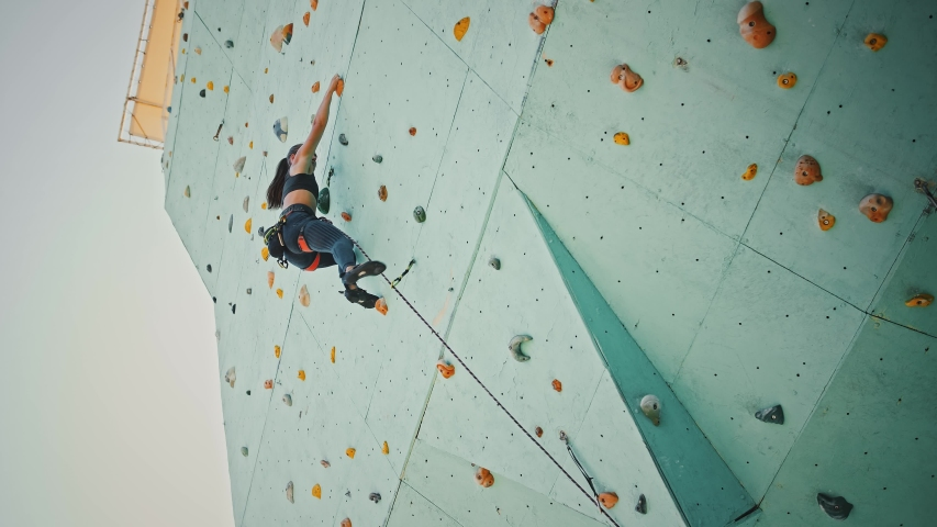Young woman climbing up, then coming down from rocky wall indoors, below view.