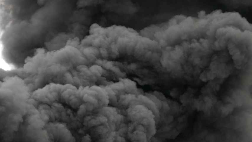 Black, dense and thick smoke column, highly polluting from a fire caused by a disaster, terrorist attack, bomb, generates an atmosphere of horror, pollution, impossible to control 4k at 59.94 frames