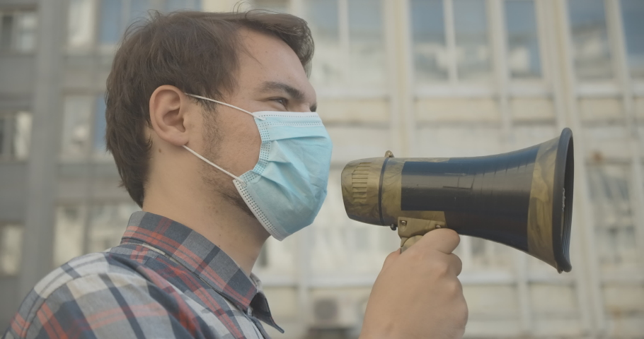 Side view of young male activist in face mask shouting through megaphone. Close-up portrait of confident man protesting in urban city on Covid-19 pandemic. Cinema 4k ProRes HQ.