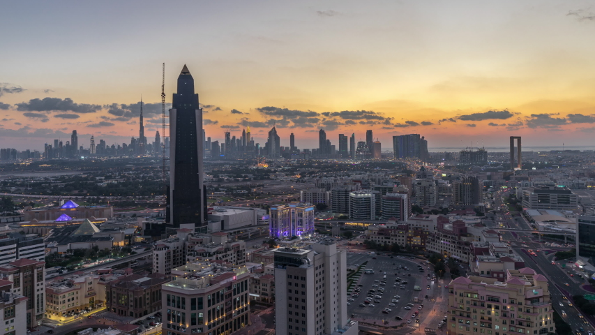 Aerial city view at warm evening with downtown and financial center towers, transition from day to night Timelapse in illuminated Dubai city, United Arab Emirates after sunset