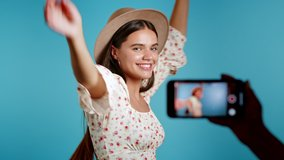 Smiling vlogger woman recording video of herself dancing in front of smartphone camera on blue background. Influencer makes funny social media clip