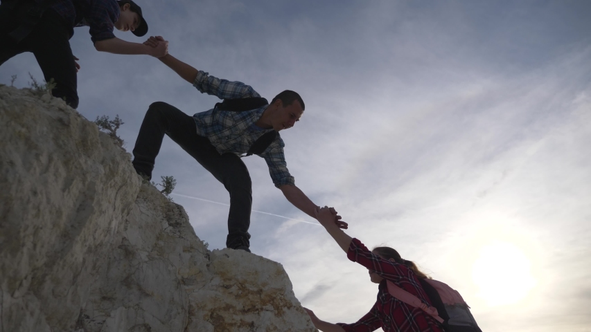 Teamwork business group. Travel partners climb to top. Group of tourists lend helping hand while climbing to top of mountain. Helping hand in business. Climbing teamwork concept. Climb friend hand Royalty-Free Stock Footage #1058184721