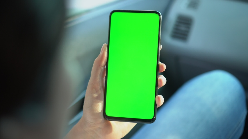 Close up of a woman's hand holding a mobile telephone with a vertical green screen in car chroma key smartphone technology cell phone street touch message display hand