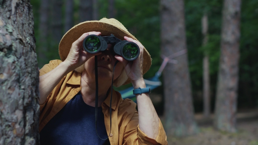 Old woman travel explorer in summer hat using binoculars watching animals in distance then hide behind the tree getting scared.