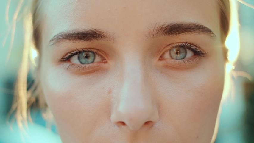 At sunlight face young beautiful woman with blue eyes smiling look at camera outdoors beauty macro natural woman hair eyes human eyebrow slow motion