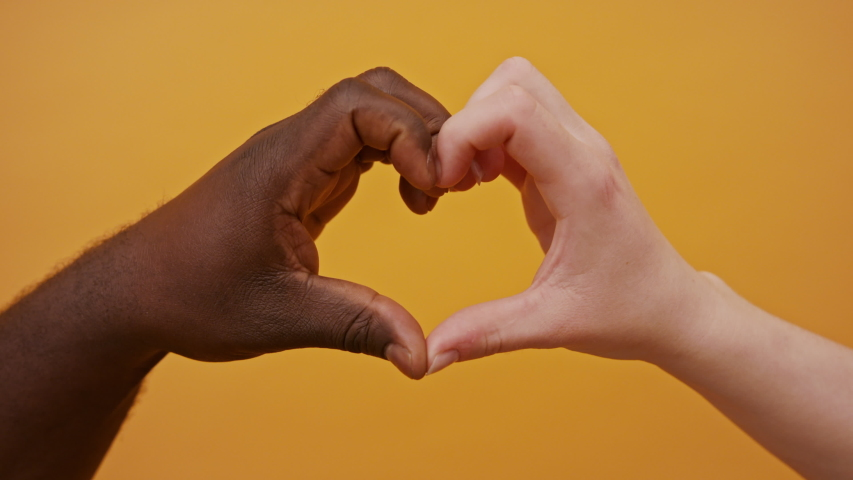 black and white hands forming heart shape together isolated on the orange background. Close up. Royalty-Free Stock Footage #1058195953