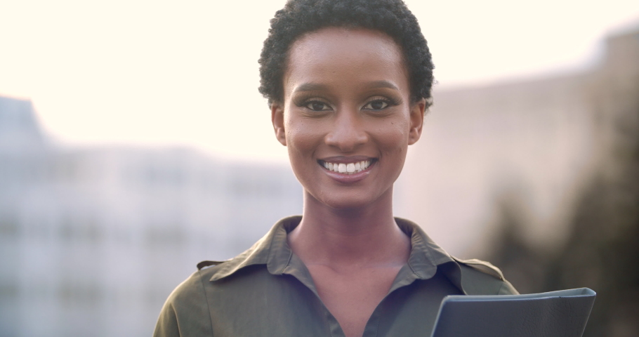 Head shot of smiling white teeth female attractive face, American African business woman student banker stands in front of camera, looks sincerely, holds documents in hands, concept of success
