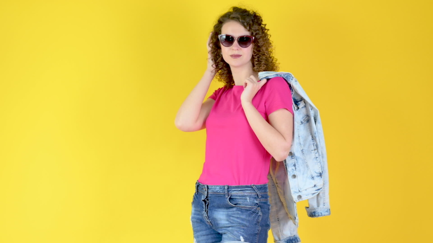 Portrait of a Young Attractive Girl with Brown Hair in Sun Glasses Smiling and Winking on a Yellow Background. Emotions of people. | Shutterstock HD Video #1058207440