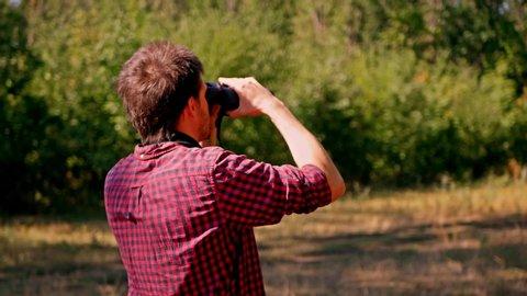 Man looking through binocular at the forest. Bird watching. Nature explore. Hiking tourist.